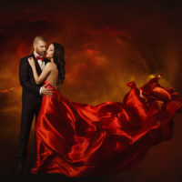 Elegant Couple Dancing in Love Woman in Red Clothes and Lover Man in Classic Suit Long Waving Dress Tail Fashion Beauty Portrait