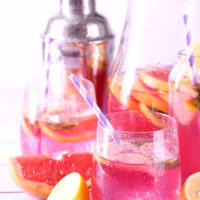 Pink lemonade in glasses and pitcher on table close-up